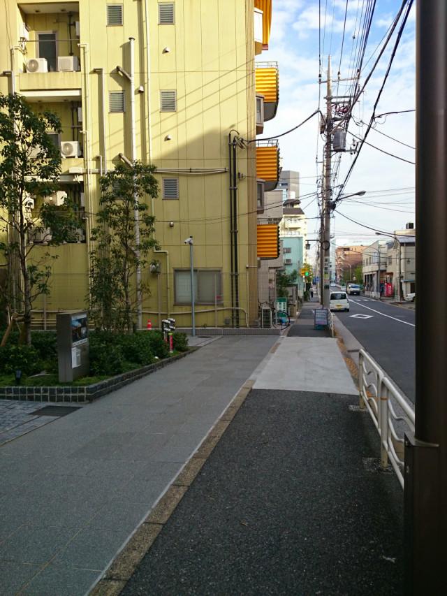 ⑤直進50メートル、黄色いベランダのマンション